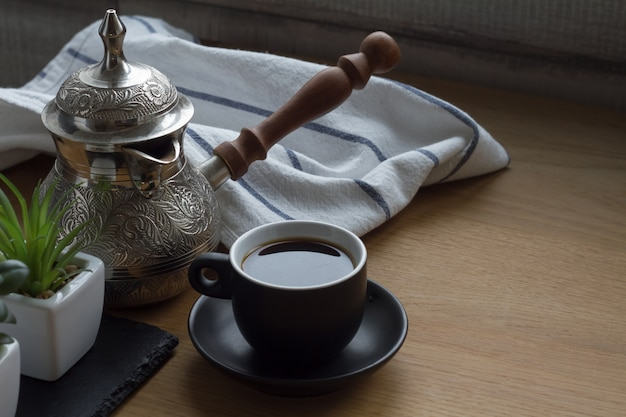 Café recién hecho en cezve, cafetera tradicional turca, taza de café, suculenta.
