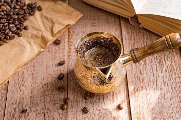 Café recién hecho en cezve libro abierto y granos de café en la mesa de madera.
