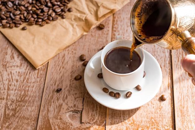 Café recién hecho en cezve la mano de la mujer vierte café en una taza blanca