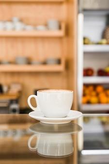 Café recién hecho en una taza blanca sobre un mostrador de vidrio