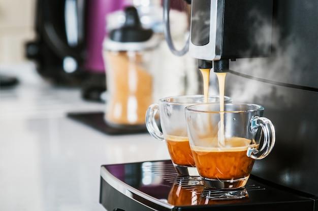 El café recién hecho se vierte de la máquina de café en vasos de vidrio.