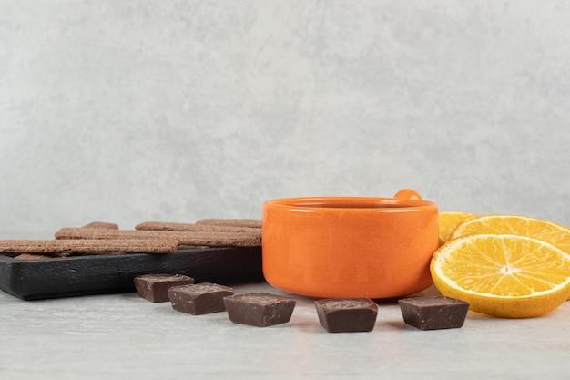 Café, rodajas de naranja, chocolate y galletas sobre superficie de mármol.
