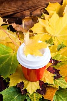 Café rojo para ir taza con hoja de marple en la parte superior. estado de ánimo de otoño