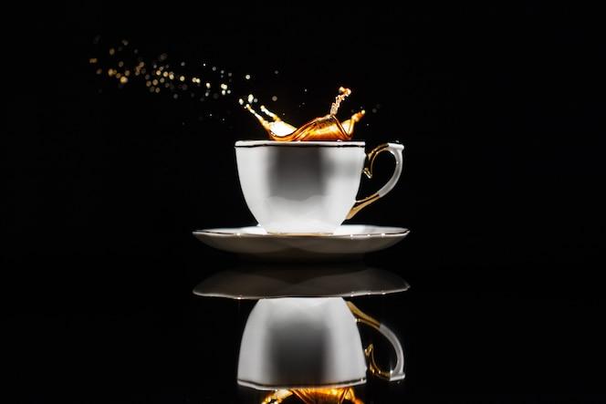 Café salpica en taza blanca sobre fondo negro