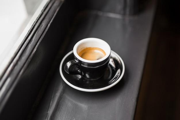 Café sobrante en taza negra en el alféizar de la ventana