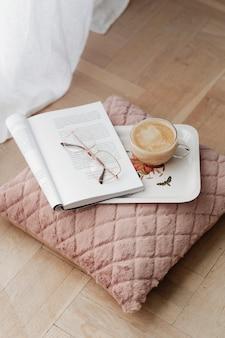 Café sobre un cojín de terciopelo rosa con una revista abierta.
