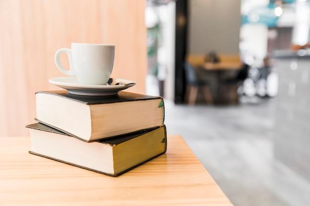 Café sobre libros sobre mesa de madera en tienda de café