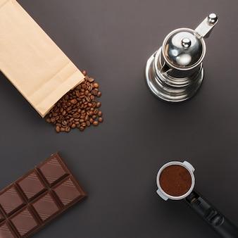 Café en un soporte, granos de café, barra de chocolate, cafetera