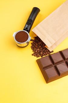 Café en un soporte, granos de café, barra de chocolate sobre fondo amarillo
