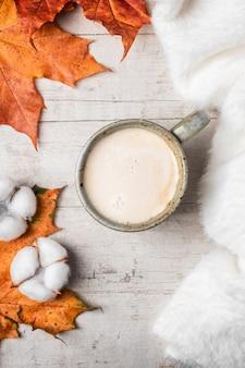 Café, suéter blanco esponjoso sobre un fondo blanco y hojas de otoño de arce.
