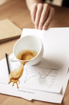 Café en taza blanca derramando sobre la mesa en la mañana, día de trabajo en la mesa de oficina
