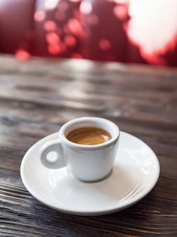 El café en una taza blanca se encuentra en una mesa de madera. hermosa vista minimalista con una taza de café en un café soleado.