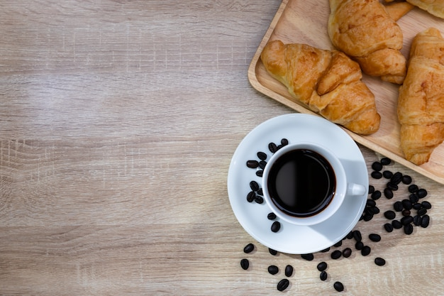 Café en taza blanca con granos de café y cruasanes en la mesa de madera, concepto de desayuno