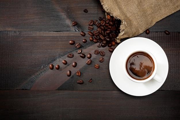 Café en una taza blanca y granos de café sobre la mesa.