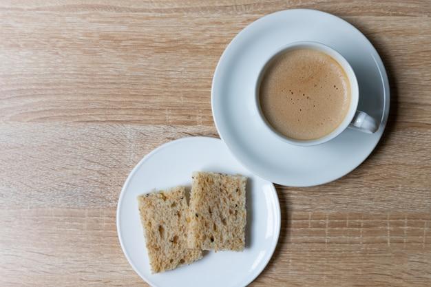 Café en taza blanca con pan integral en mesa de madera, desayuno con concepto saludable
