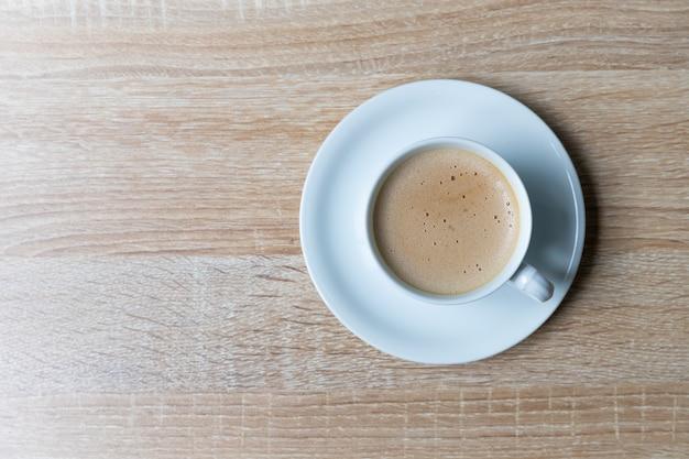 Café en taza blanca sobre mesa de madera, concepto de desayuno