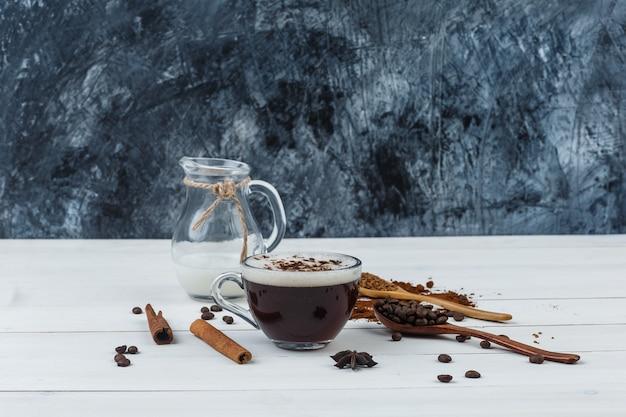 Café en una taza con café molido, granos de café, canela en rama, vista lateral de la leche sobre fondo de madera y grunge