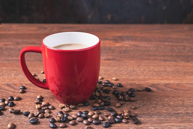 Café en una taza de café rojo sobre una mesa de madera