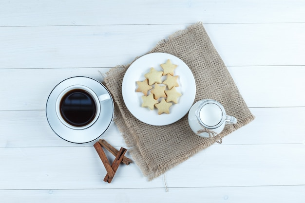 Café en una taza con galletas, canela en rama, vista superior de la leche en madera y un pedazo de fondo de saco