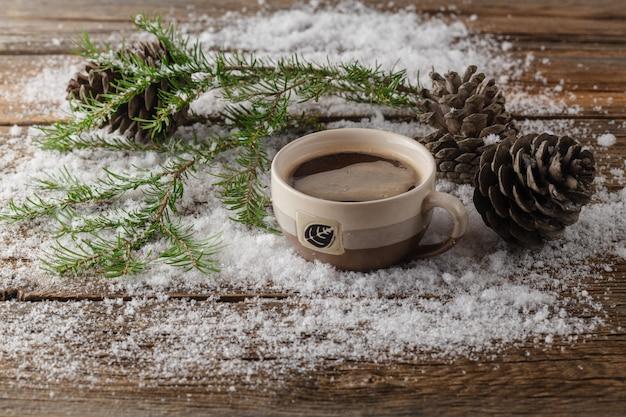 Café en una taza, nieve, árbol