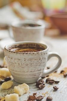 Café en una taza pequeña con azúcar moreno de caña y azúcar en terrones