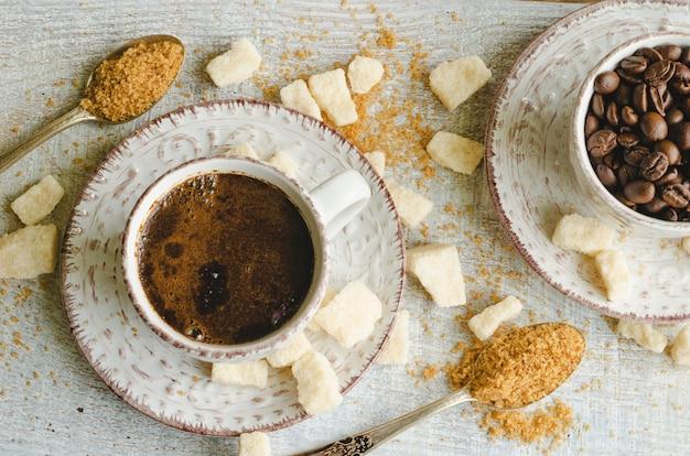 Café en una taza pequeña con azúcar moreno de caña y azúcar en trozos sobre madera gris
