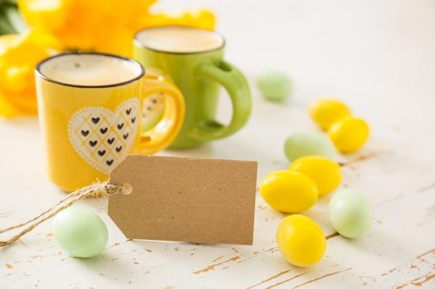Café en tazas verdes y amarillas, tulipanes.