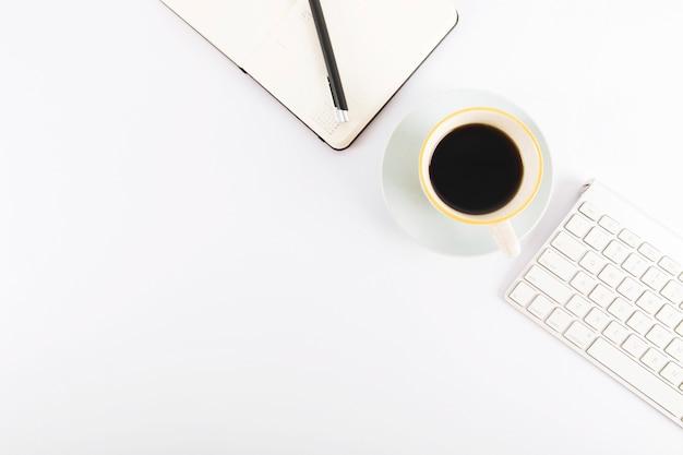 Café entre el teclado y el cuaderno