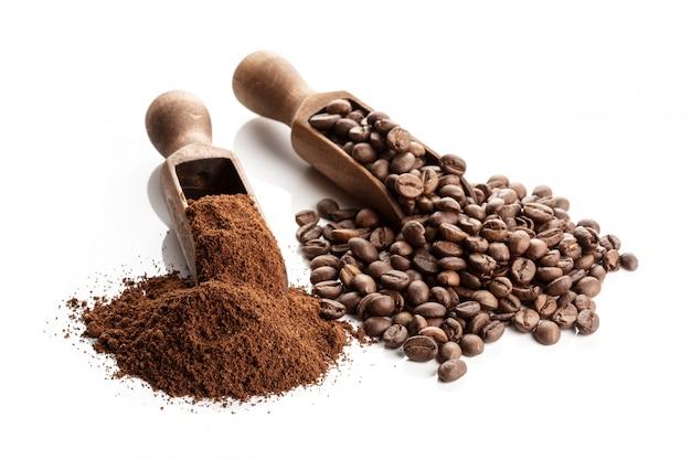 Café tostado en grano y molido aislado sobre fondo blanco.