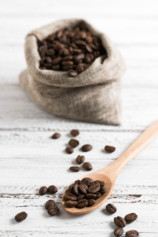Café tostado en grano en saco de arpillera y cuchara
