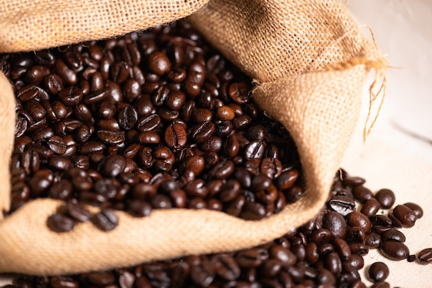 Café tostado en grano en saco de arpillera.