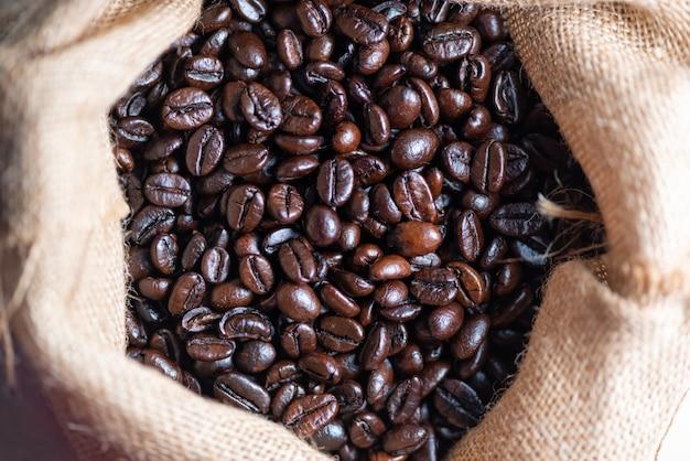 Café tostado en grano con saco de arpillera.