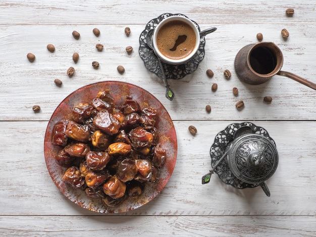 Café turco con fechas y cardamomo en la mesa de madera.