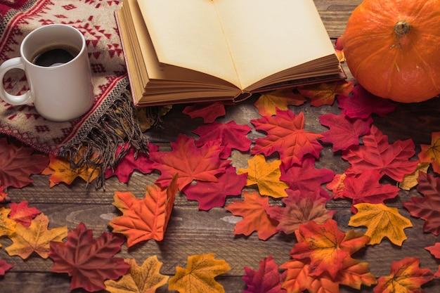 Café y manta cerca de libro y calabaza