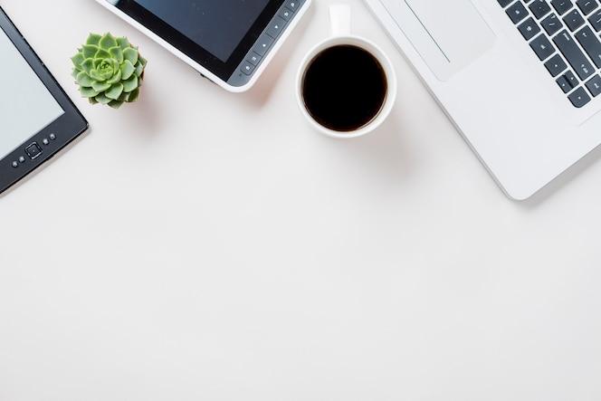 Café y planta cerca de computadoras portátiles y libros electrónicos