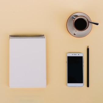 Café y teléfono inteligente cerca del portátil