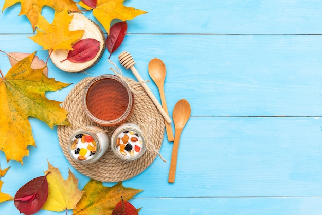 Café con yogur en la mesa con hojas de otoño.