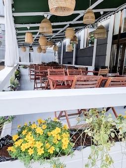 Cafés en la calle en ausencia de gente. cuarentena mesas y sillas de madera vacías en la calle fuera de un bar cafetería o restaurante con rayos de sol, lámparas de paja. el concepto de amor y cena romántica.