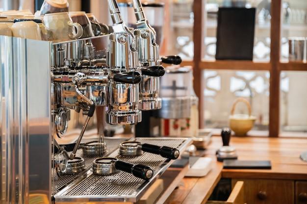 Cafetera grande de aluminio con dos molinillos en barra de madera.