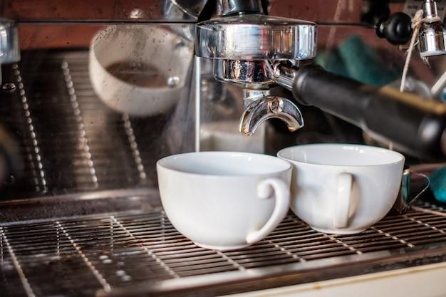Cafetera haciendo café espresso en taza blanca en el mostrador