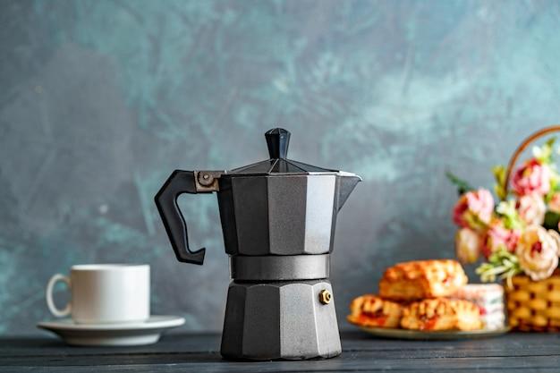 Cafetera de moca, flores y dulces en superficie oscura para la hora del café