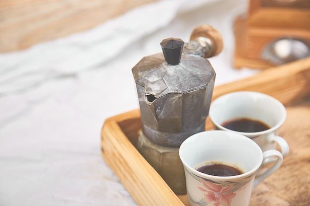 Cafetera moka con dos tazas de café en bandeja de madera