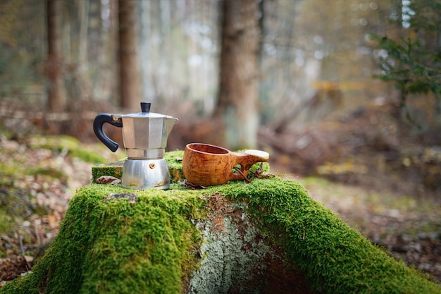 Cafetera de olla moka y taza de madera kuksa sobre un hermoso tocón cubierto de musgo.