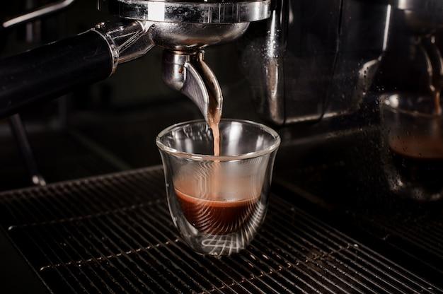 Cafetera profesional que vierte un café fresco y aromático en una taza