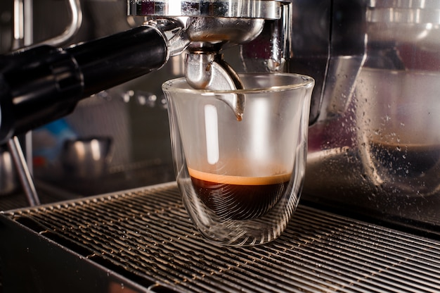 Cafetera que vierte un café fresco y aromático en una taza