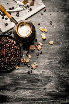Cafetera recién hecha con el periódico y granos de café tostados en la mesa de madera.