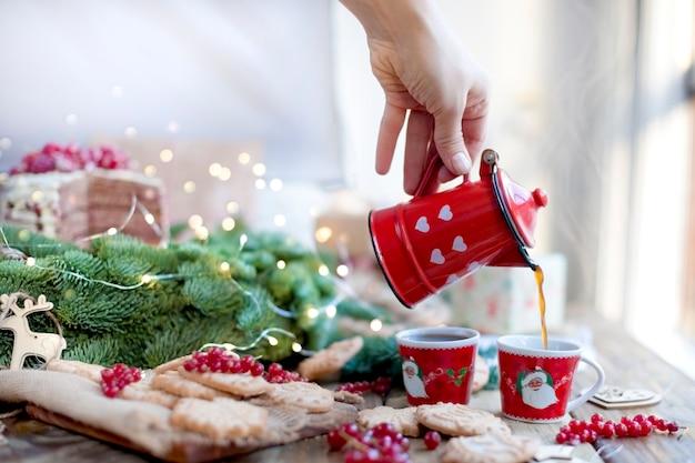 Una cafetera en sus manos vierte café, bayas y galletas, regalos, cerca de un árbol de navidad en una mesa de madera cerca de la ventana