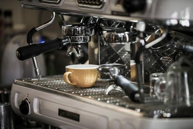 Cafetera con taza de café en el café