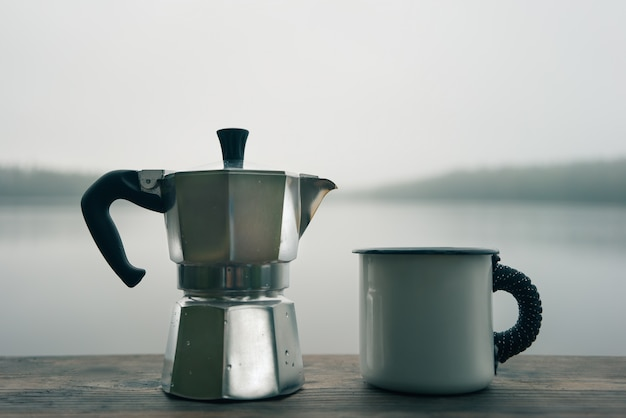 Cafetera y taza sobre una superficie de madera.