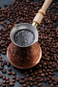 Cafetera turca jezve con café caliente en granos de café